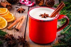 圣诞节饮料:热的白色巧克力用桂香和茴香在红色杯子 免版税图库摄影