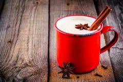 圣诞节饮料:蛋黄乳用桂香和茴香在红色杯子 免版税库存照片