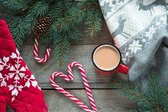 圣诞节饮料 抢劫热的咖啡用牛奶,在木背景的红色棒棒糖 新年度 另外的卡片形式节假日 土气样式 顶视图 库存照片