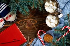 圣诞节饮料 抢劫热的咖啡用蛋白软糖,在木背景的红色棒棒糖 新年度 免版税库存照片