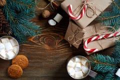 圣诞节饮料 抢劫热的咖啡用蛋白软糖,在木背景的红色棒棒糖 新年度 图库摄影