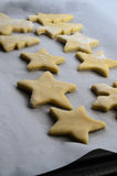 圣诞节饼干在烘烤盘子的酥皮点心形状有羊皮纸的 免版税库存照片