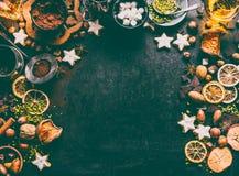 圣诞节香料、巧克力和曲奇饼背景与成份烘烤和甜食的:坚果,干果子,巧克力 库存图片
