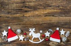 圣诞节驯鹿和圣诞老人帽子装饰 免版税库存图片