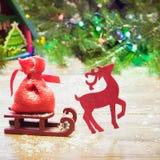 圣诞节驯鹿运载在木背景的一个雪橇与 免版税库存图片