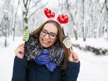 圣诞节鹿戴头受话器的年轻美丽的微笑的少妇漫步冬天的室外 冬天乐趣概念 图库摄影
