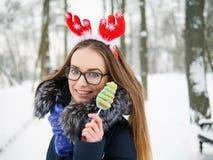 圣诞节鹿戴头受话器的年轻美丽的微笑的少妇漫步冬天的室外 冬天乐趣概念 免版税图库摄影