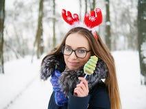 圣诞节鹿戴头受话器的年轻美丽的微笑的少妇漫步冬天的室外 冬天乐趣概念 库存照片