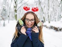 圣诞节鹿戴头受话器的年轻美丽的微笑的少妇漫步冬天的室外 冬天乐趣概念 免版税库存图片