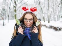 圣诞节鹿戴头受话器的年轻美丽的微笑的少妇漫步冬天的室外 冬天乐趣概念 库存图片
