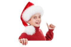 圣诞节,圣诞老人帽子的逗人喜爱的男孩指向手指的 免版税库存图片