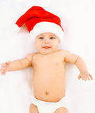 圣诞节,家庭观念-说谎在白色床上的红色圣诞老人帽子的逗人喜爱的婴孩 库存图片