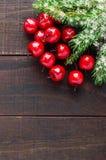 圣诞节,新年题材 绿色云杉的分支,在黑暗的木背景的装饰莓果 免版税库存照片