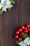 圣诞节,新年题材 绿色云杉的分支,装饰莓果,在黑暗的木背景的雪花 库存照片