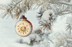 圣诞节,除夕背景-显示在多雪的杉树的新年圣诞节玻璃玩具时钟除夕, 免版税图库摄影