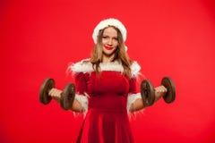 圣诞节, x-mas,冬天,幸福概念-体型 行使与在圣诞老人帮手的哑铃的坚强的适合妇女 免版税图库摄影
