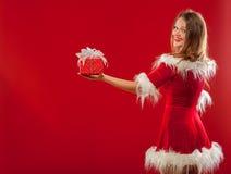 圣诞节, x-mas,冬天,幸福概念-圣诞老人帮手帽子的微笑的妇女有礼物盒的,在红色背景 免版税库存照片