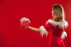 圣诞节, x-mas,冬天,幸福概念-圣诞老人帮手帽子的微笑的妇女有礼物盒的,在红色背景 免版税库存图片