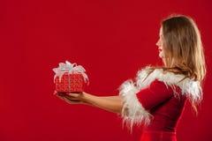 圣诞节, x-mas,冬天,幸福概念-圣诞老人帮手帽子的微笑的妇女有礼物盒的,在红色背景 库存照片