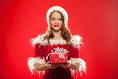 圣诞节, x-mas,冬天,幸福概念-圣诞老人帮手帽子的微笑的妇女有礼物盒的,在红色背景 免版税图库摄影