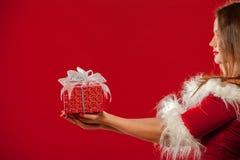 圣诞节, x-mas,冬天,幸福概念-圣诞老人帮手帽子的微笑的妇女有礼物盒的,在红色背景 库存图片