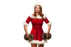 圣诞节, x-mas,冬天,幸福概念-体型 行使与在圣诞老人帮手的哑铃的坚强的适合妇女 库存图片