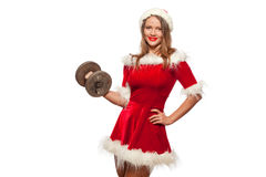 圣诞节, x-mas,冬天,幸福概念-体型 行使与在圣诞老人帮手的哑铃的坚强的适合妇女 库存照片