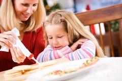 圣诞节:作为母亲的女孩手表用管道输送在曲奇饼上的结冰 免版税库存照片