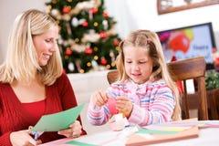 圣诞节:做纸链子的家庭的工艺乐趣 图库摄影