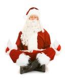 圣诞节:圣诞老人在一个冥想的姿势坐 库存图片
