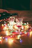 圣诞节:在桌上的红葡萄酒与五颜六色的光 免版税库存照片