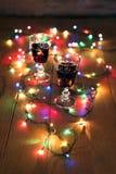 圣诞节:在桌上的红葡萄酒与五颜六色的光 库存图片