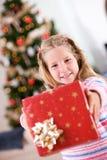 圣诞节:女孩提供相当被包裹的圣诞节礼物 库存图片