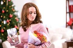 圣诞节:妇女接受了节日礼物的花 免版税库存图片