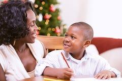 圣诞节:帮助的母亲给圣诞老人写信 库存图片