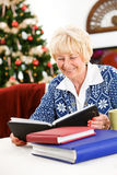 圣诞节:资深妇女看象册 库存照片