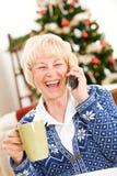 圣诞节:跟上电话的妇女朋友 免版税库存照片