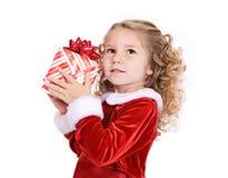 圣诞节:逗人喜爱女孩猜测什么在礼物 免版税库存照片