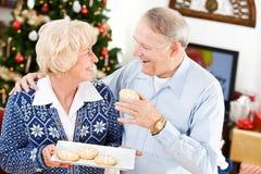 圣诞节:采取假日曲奇饼的丈夫 免版税库存照片