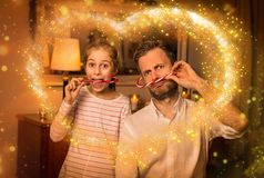 圣诞节-使用与棒棒糖的父亲和女儿 免版税库存照片