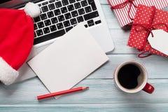 圣诞节贺卡、礼物盒、个人计算机和咖啡杯在木头 免版税库存图片