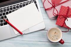 圣诞节贺卡、礼物盒、个人计算机和咖啡杯在木头 图库摄影