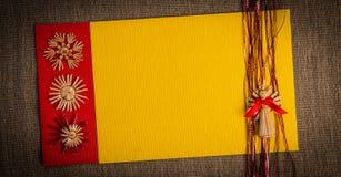 圣诞节贺卡假日秸杆装饰,红色和黄色颜色的背景构造了纸 免版税库存照片