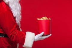 圣诞节 圣诞老人手套的手照片有一个红色桶的用玉米花,在红色背景 免版税库存照片
