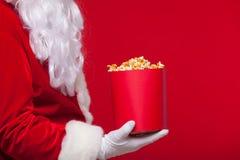 圣诞节 圣诞老人手套的手照片有一个红色桶的用玉米花,在红色背景 免版税库存图片