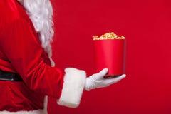 圣诞节 圣诞老人手套的手照片有一个红色桶的用玉米花,在红色背景 库存图片