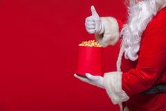 圣诞节 圣诞老人手套的手照片有一个红色桶的用玉米花,在红色背景 免版税图库摄影