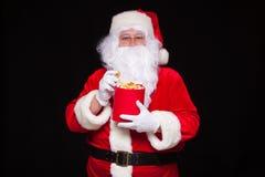 圣诞节 圣诞老人手套的手照片有一个红色桶的用玉米花,在黑背景 免版税库存照片