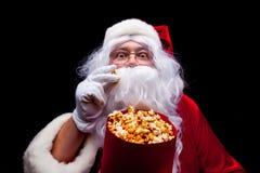 圣诞节 圣诞老人手套的手照片有一个红色桶的用玉米花,在黑背景 免版税库存图片