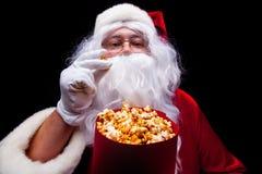 圣诞节 圣诞老人手套的手照片有一个红色桶的用玉米花,在黑背景 免版税图库摄影
